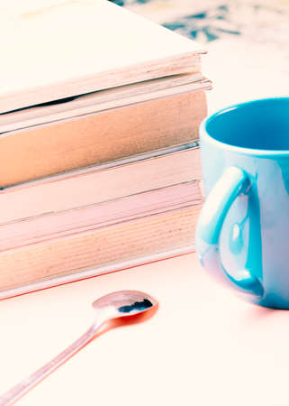 Literature concept. White books with a blue cup on a pink background. Фото со стока