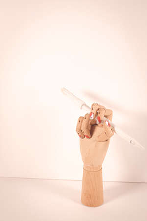 Wooden hand holding a white paintbrush on white background.