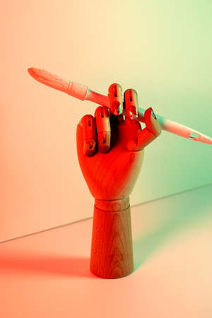 Wooden hand with a white paintbrush with red and green lights.