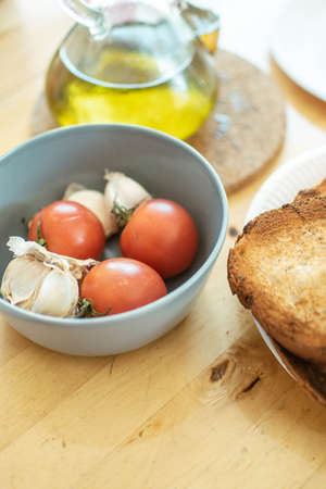 Mediterranean diet concept. Bowl with tomatoes and garlic along with an oil can and toast.