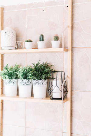 Metal pots with decorative plastic plants on a shelf.