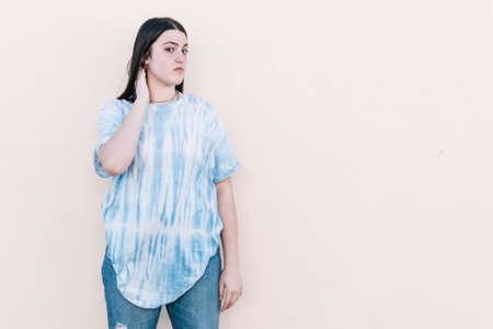 Teen girl in a tie dye t-shirt on a pinched orange wall