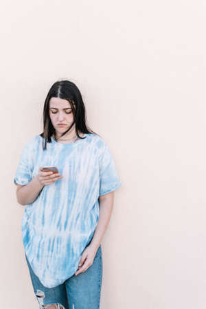 Teen girl in a tie dye shirt on a pinched orange wall looking at the smartphone