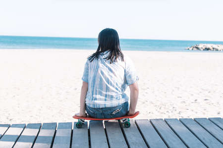 Teen girl in a tie dye shirt sitting on a skateboard looking at the beach