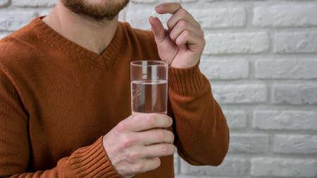 Vitamin Rating. Man drinking a pill