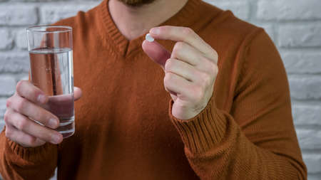 Man takes medicine with a glass of water. White pill in a young male hand