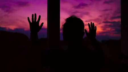 A guy looks at a beautiful sunset from the window of his apartment. Pink sunset.Very beautiful landscape.A man admired the dawn