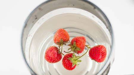 Ripe strawberries in water in a glass. Top view, close-up.