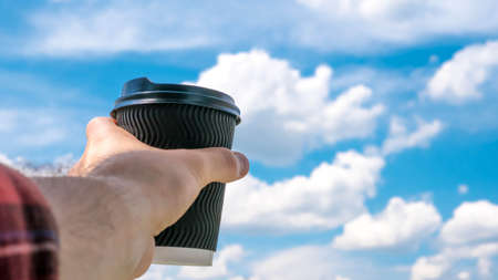 A glass of coffee on a background of the sky and in hand, drinking coffee in a plastic glass, delicious drink, close-up.