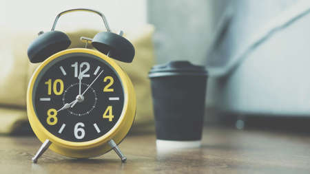 Retro clock, arrows show 8 am, a glass of coffee in the background, close-up. Stockfoto