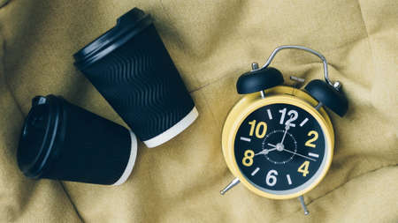 Retro clock with alarm clock and cappuccino, black coffee americano, drink concept, aromatic coffee, top view.Plastic cup for coffee.