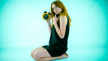 Young and beautiful girl in a dress, a retro watch in her hands, close-up.