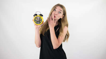 Portrait of a girl with a retro clock in her hands, a cute and young girl in a black dress on a white background, close-up.