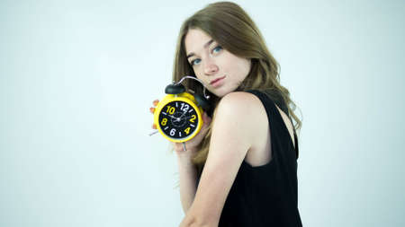 A girl with a discerning look, looks into the lens camera, a young lady with a retro clock, on a white background.