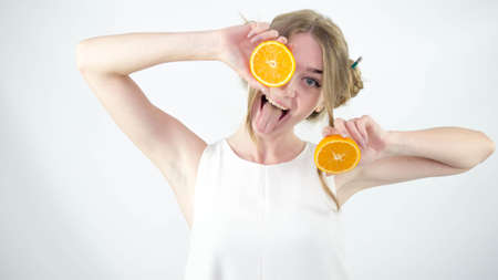 A young and beautiful girl with a smile holds oranges in her hands, on a white background, close-up.