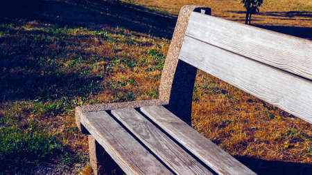 Wooden bench in warm summer colors, bench without people, close-up.
