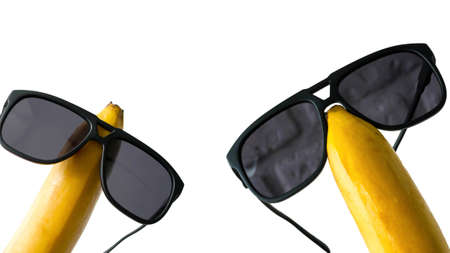 Sun goggles dressed on a banana head, funny fruits in glasses, isolated on white, close-up