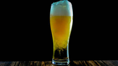 Light beer in a beer glass on a black background close-up, pouring fresh beer into a glass.