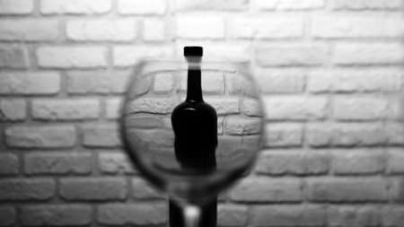 Empty wine glass with a bottle of wine on a white brick wall background. 写真素材