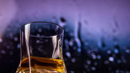 Whiskey in a glass on a colorful background with bokeh effect, Alcoholic drink in a glass, close-up