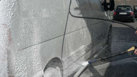 Car wash, a worker washes the car, a man pours foam on the car, washes away the dirt. Stock fotó