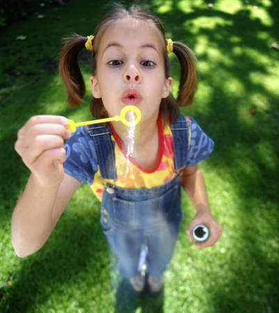 Girl blowing bubbles standing on green lawn wearing overalls
