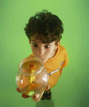 Boy holding fish bowl with goldfish standing on green background photo