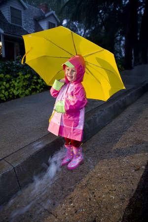girl in rain: Little girl with yellow umbrella playing in rain wearing pink rain slicker and pink galoshes Stock Photo