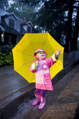 slicker: Little girl with yellow umbrella playing in rain wearing pink rain slicker and pink galoshes Stock Photo