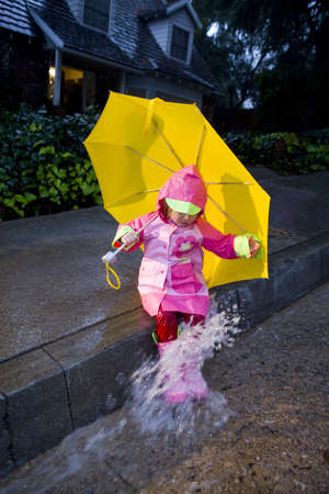 Little girl with yellow umbrella playing in rain wearing pink rain slicker and pink galoshes photo