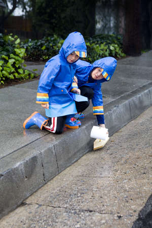 slicker: Young boys playing with toy boat in the rain wearing rain slickers and golashes. Stock Photo