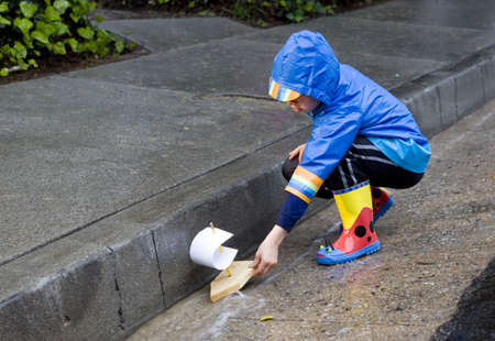 Young boy playing with toy boat in the rain wearing rain slickers and golashes. Banque d'images