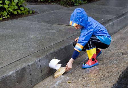botas de lluvia: Ni�o jugando con barco de juguete en la lluvia vistiendo slickers de lluvia y golashes.