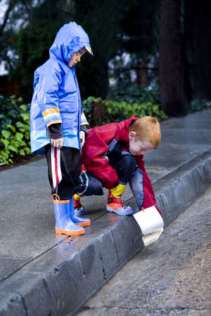 Young boys playing with toy boat in the rain wearing rain slickers and golashes. photo