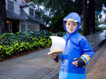 slicker: Young boy playing with toy boat in the rain wearing rain slicker and golashes.