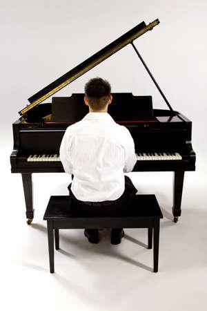 白いシャツとピアノのベンチに座って黒のズボンを着てのグランド ピアノを持つ男。