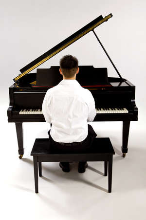 Man with Grand piano wearing white shirt and black pants sitting at piano bench. photo