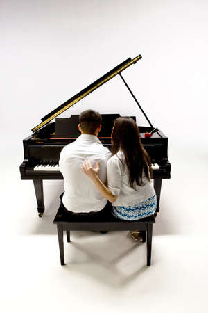Couple with Grand piano 1 in white shirt, black pants and sundress sitting at piano bench with red rose. photo