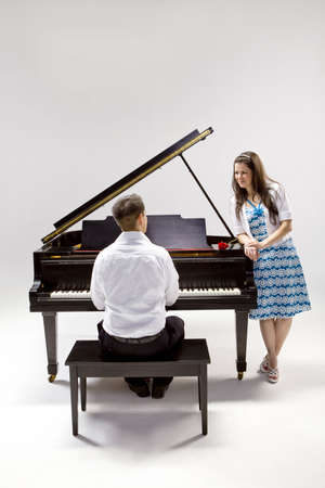 Couple with Grand piano 2 in white shirt, black pants and sundress with red rose. photo