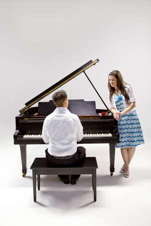 Pareja con gran piano 2 en camisa blanca, pantalón negro y sundress con rosa roja. Foto de archivo - 7109977
