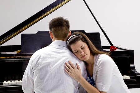 Couple with Grand piano 4 sitting at piano bench with red rose. Stock Photo - 7109976