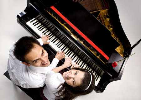 Couple with Grand piano 6 sitting at piano bench with red rose. photo