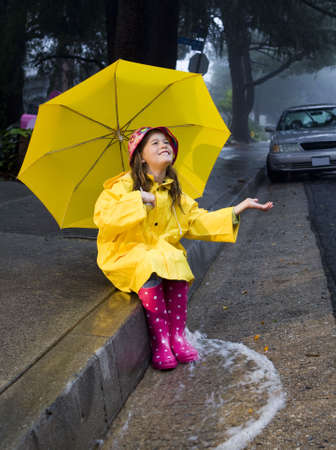 Young girl playing in the rain with yellow umbrella
