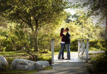 pareja besandose: Cauc�sica pareja bes�ndose en puente  Foto de archivo