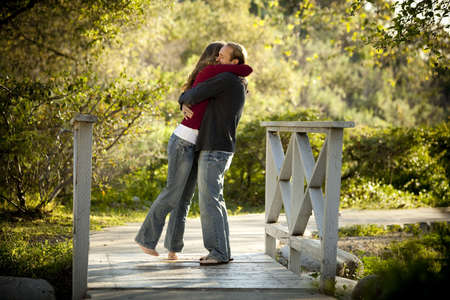 engagement: Caucasian couple hugging on bridge
