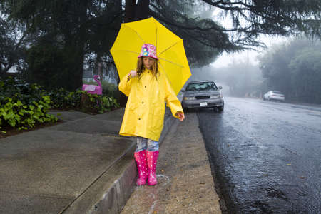 Young girl playing in rain with yellow umbrella photo