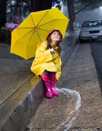 Young girl playing in rain with yellow umbrella 2 photo