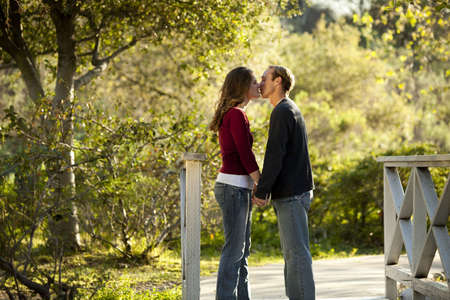 Caucasian couple in love kissing on wooden bridge