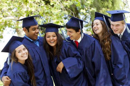 微笑し、バック グラウンドで木とキャップとガウンで笑って卒業生 写真素材