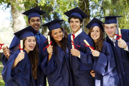 Étudiants diplômés souriant et le rire avec les diplômes ; arbres en arrière-plan